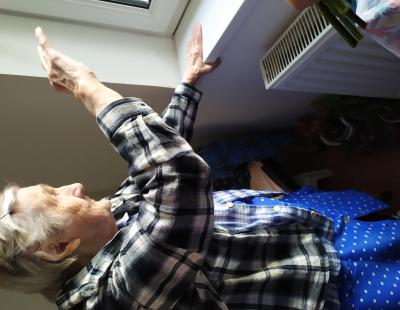 Aszalós néni integet kifelé a hozzátartozóiknak 90. születésnapján