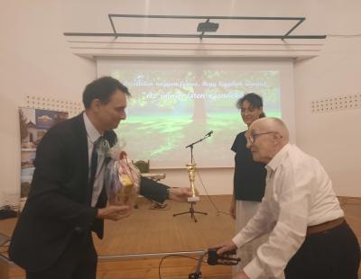 Az Országos Papi Otthon férfi kórusának képviselője átveszi az első helyezettnek járó díjat